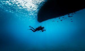 Taucher mit Kameraquipment unter Tauchboot